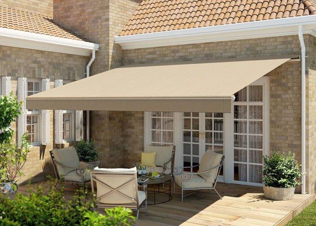 Large, tan awning covering backyard patio