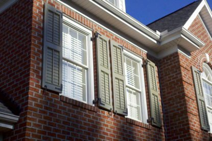 Gray exterior shutters on brick home