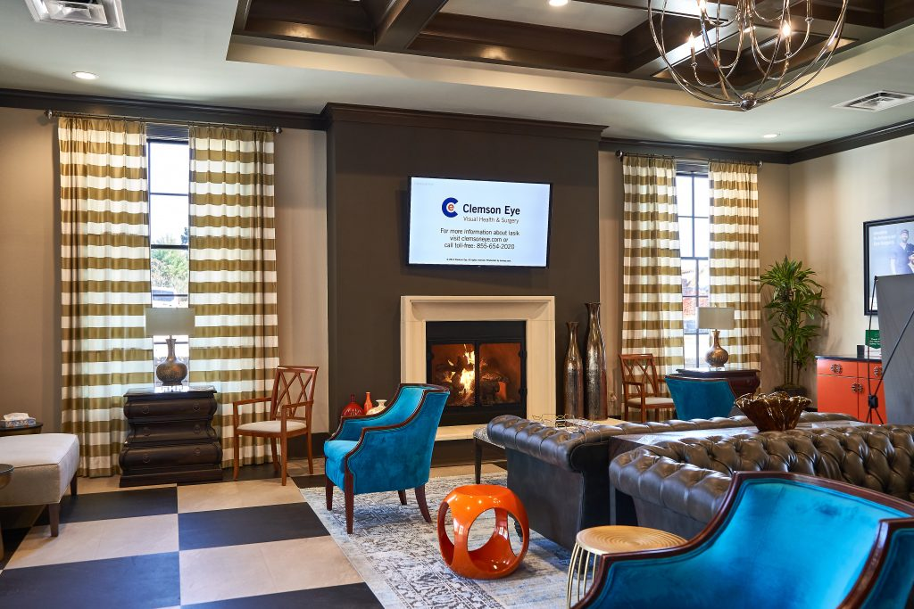 Waiting room with fire place, large windows with decorative blonds, luxury furniture